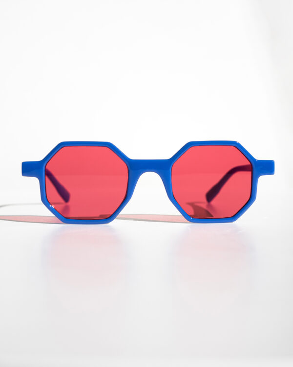Blue Geometric Sunglasses with pink lenses rest on a white surface.
