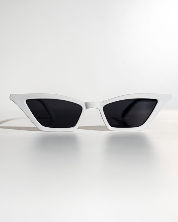 White Cat-Eye Sunglasses with black lenses rest on a white surface.