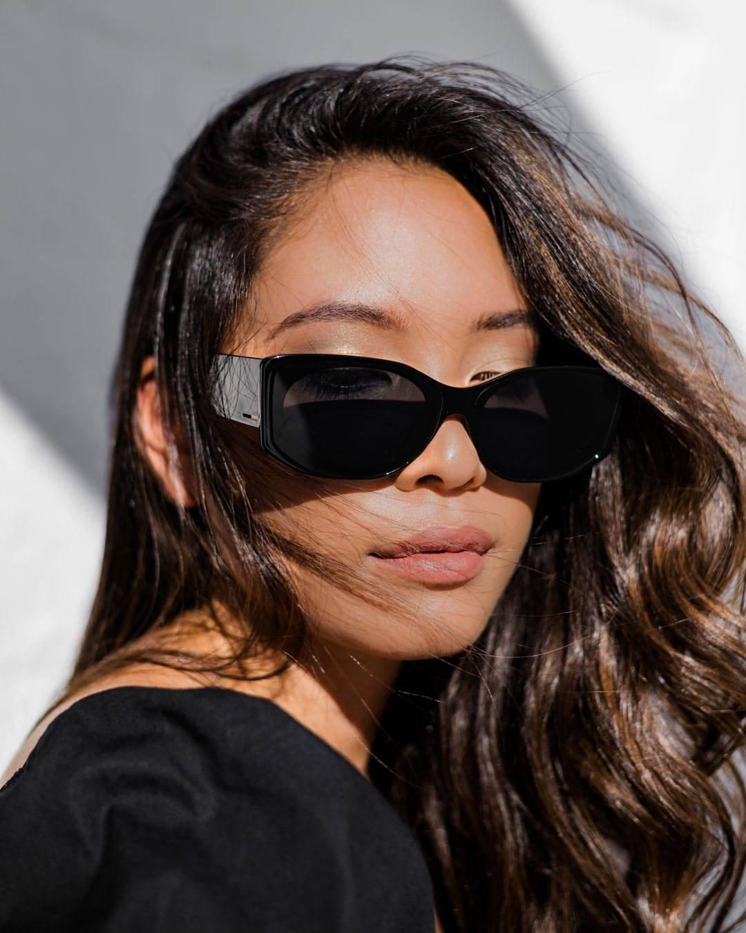 A woman with long dark hair wears and oval sunglass shape.