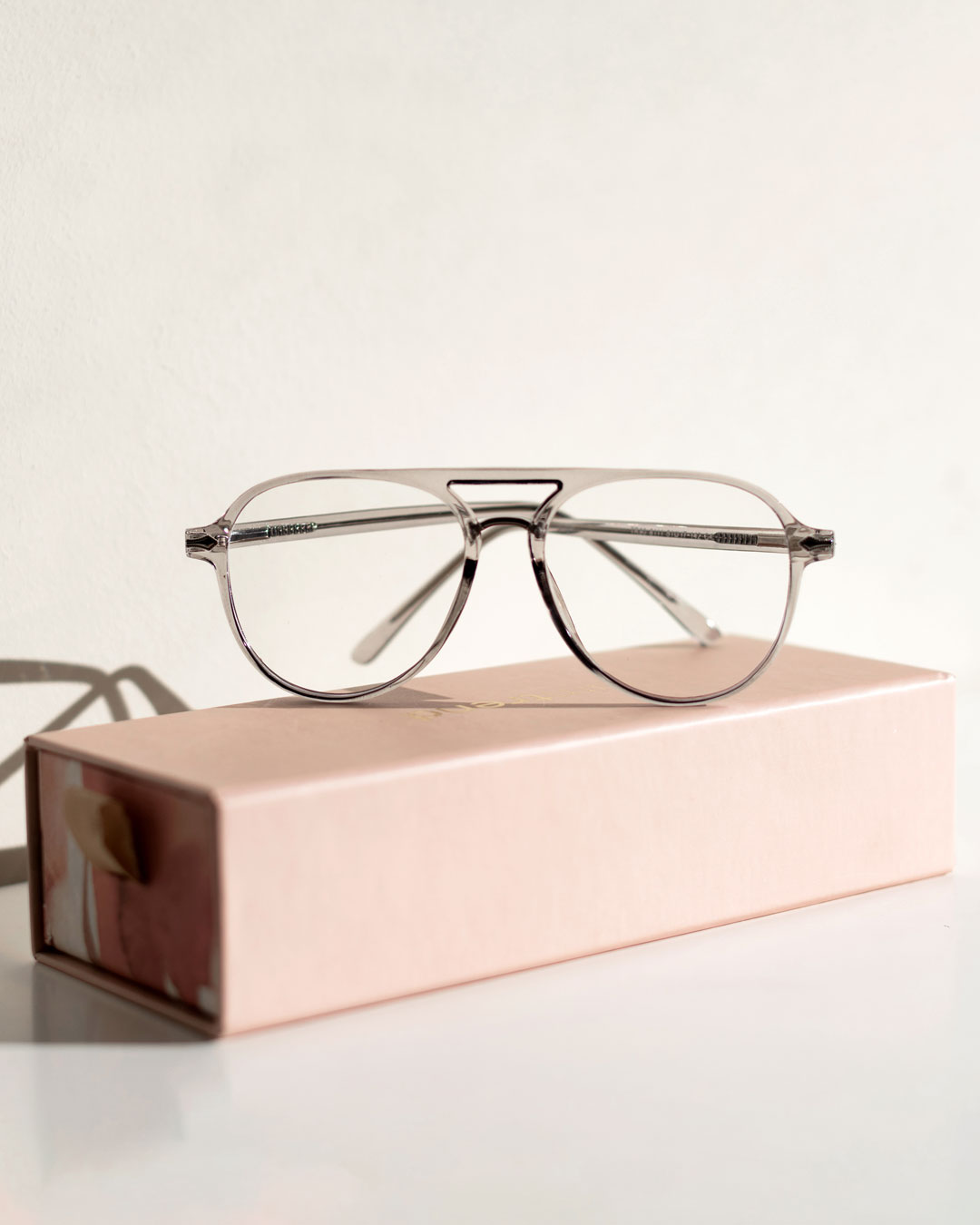 Aviator blue light glasses with a transparent frame rest on top of a pink iamtrend case.