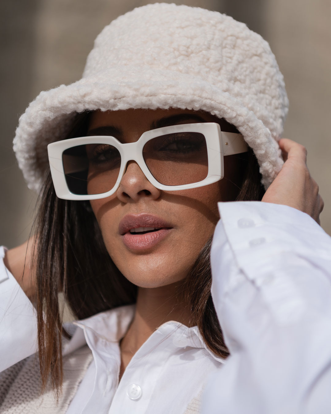 Sunglasses with a rectangular shape worn by a young woman wearing a white hat.