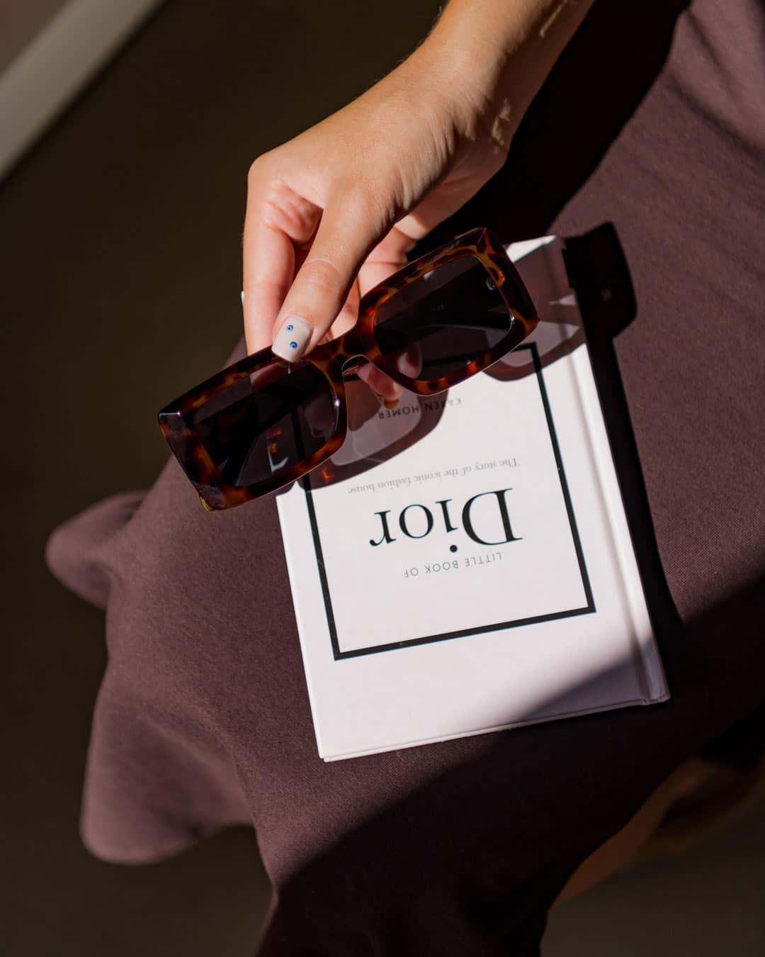 rectangle tortoise shell sunglasses on a book