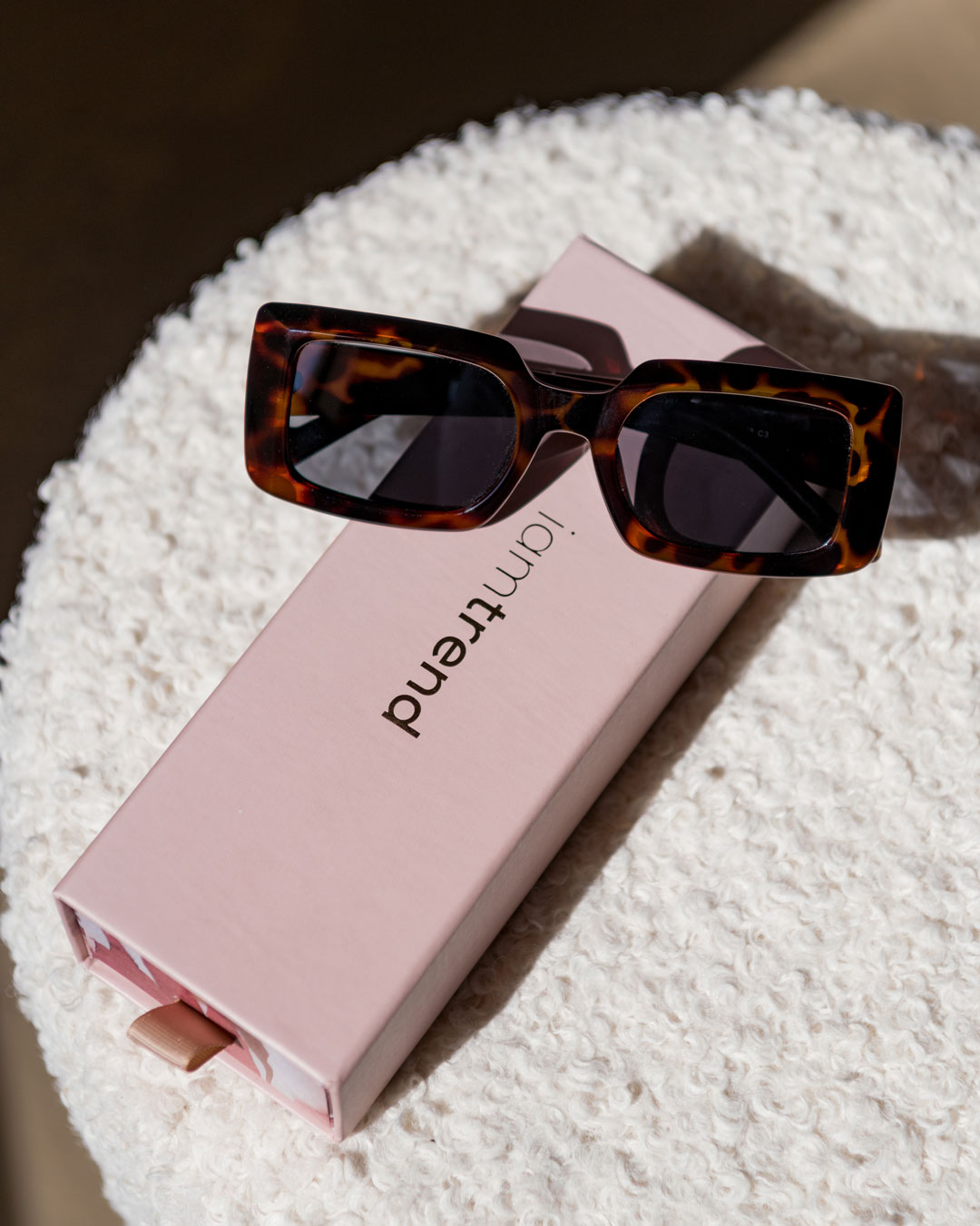 tortoise shell sunglasses on a pink box