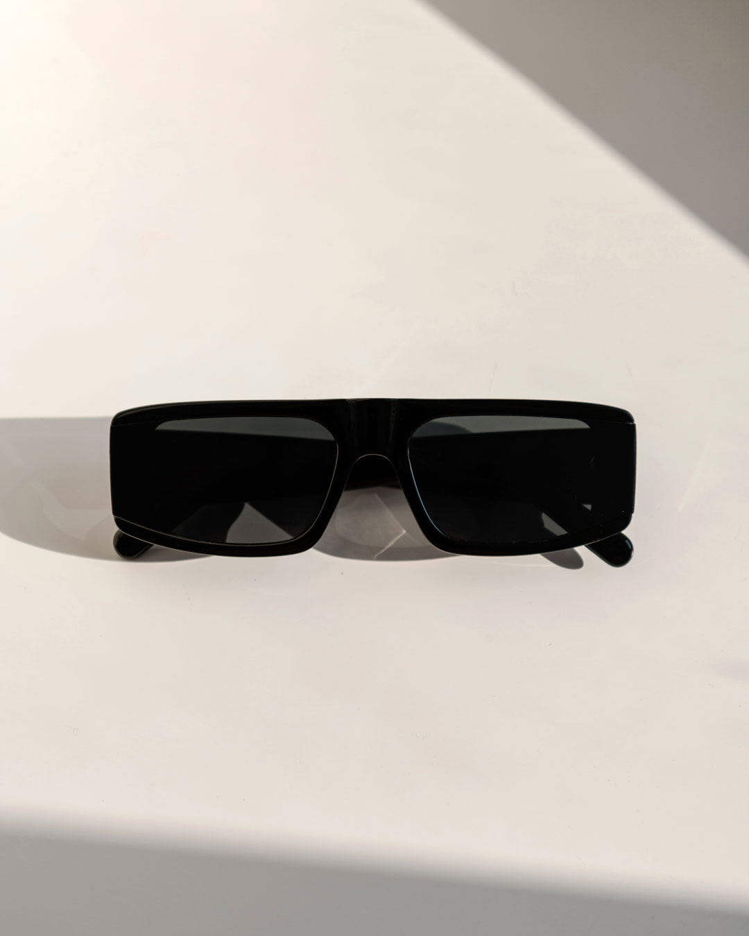 Rectangle black sunglasses on a white table
