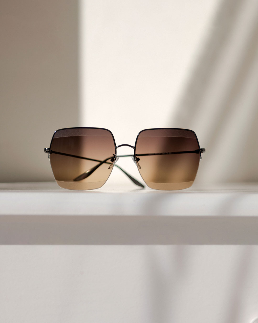 Brown ombre sunglasses with a metal frame rest of a white surface