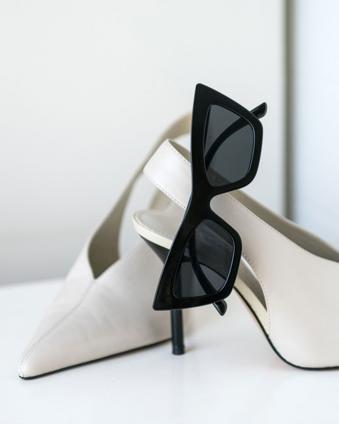 Black cat-eye sunglasses with UV400 protective lenses hang from a white heel.