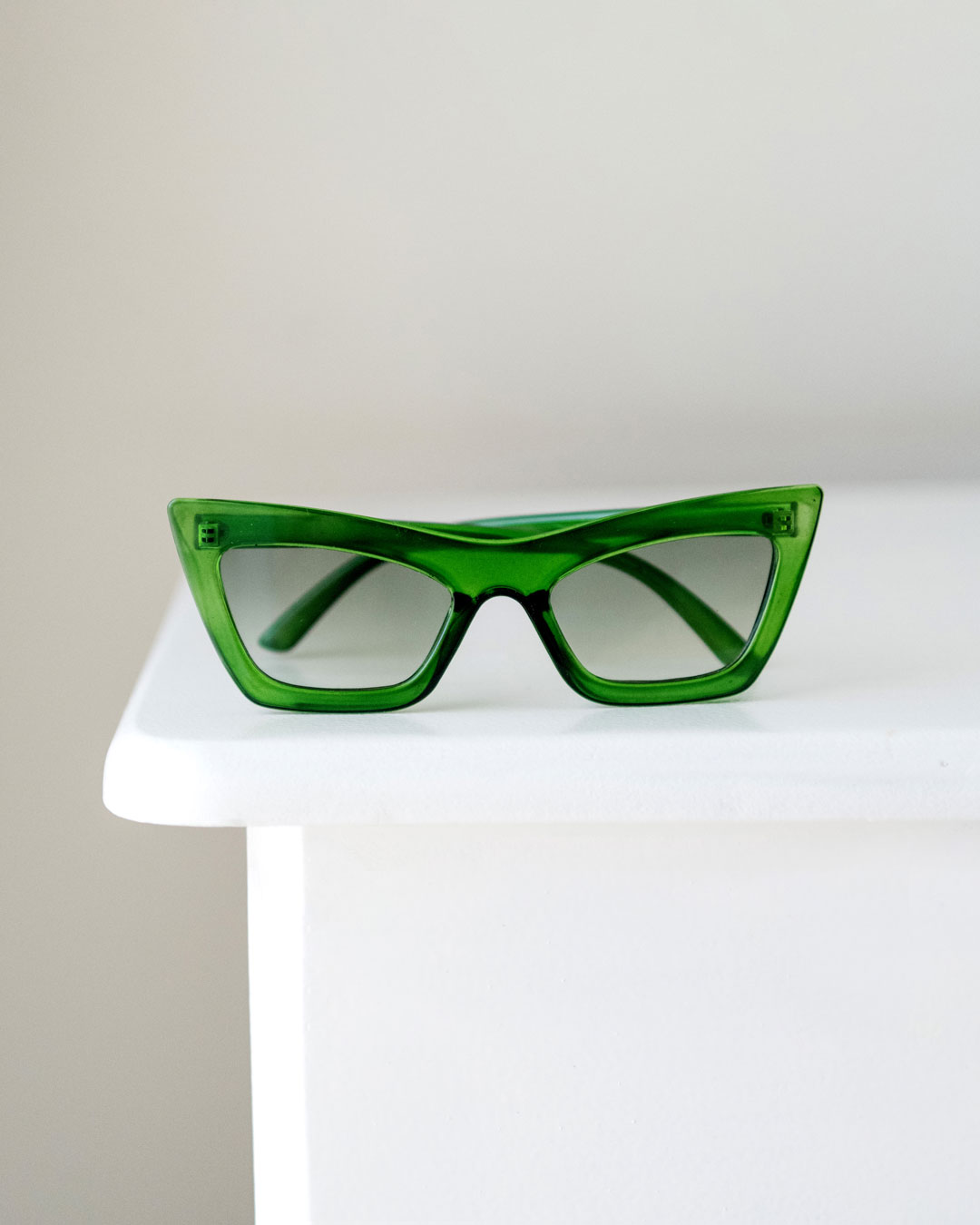 An emerald green cat-eye sunglass style sits on top of a white table.