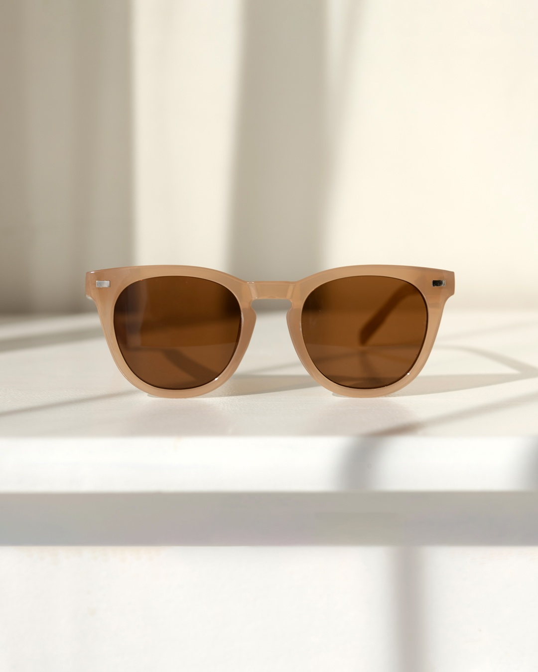 Neutral Sunglasses with a mocha coloured frame and brown lens tint sit on top of a white surface.