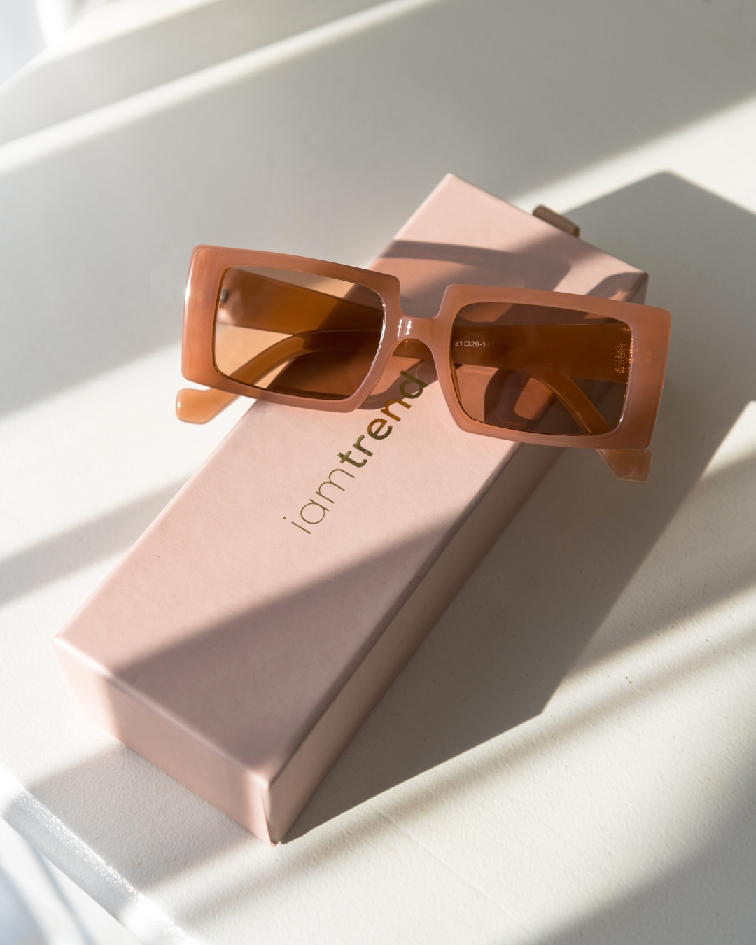 Rectangular sunglasses with a terracotta frame and lens tint sits on a pink iamtrend keepsake box.
