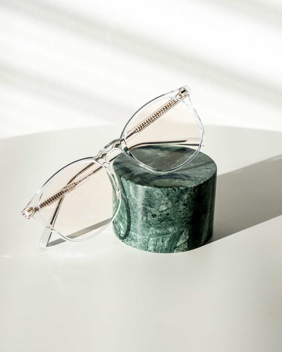 Clear framed glasses fitted with anti-blue light lenses and gold-toned metal detailing propped up against a green marble circle.