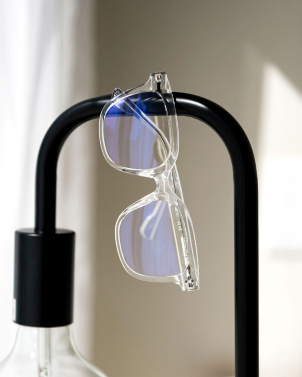 Square shaped glasses with clear frames hanging from a black metal lamp.