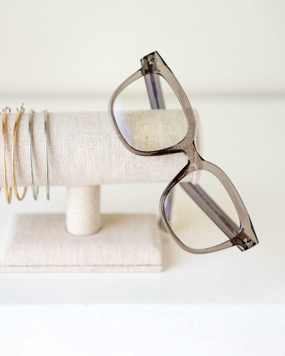 Grey square-shaped glasses with anti-blue light lenses hang from a jewellery stand.