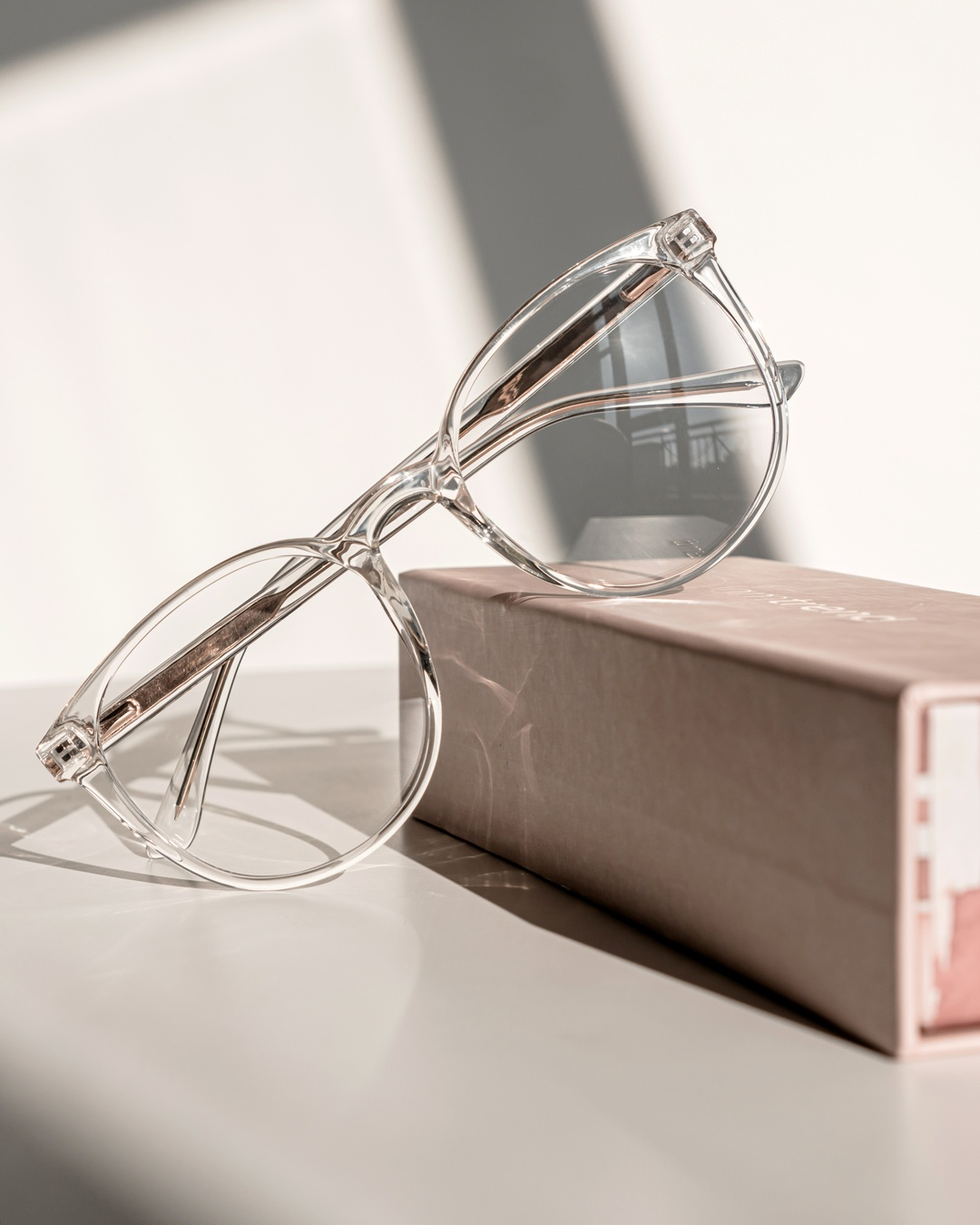 Oversized glasses with clear frames propped up against a pink iamtrend box.
