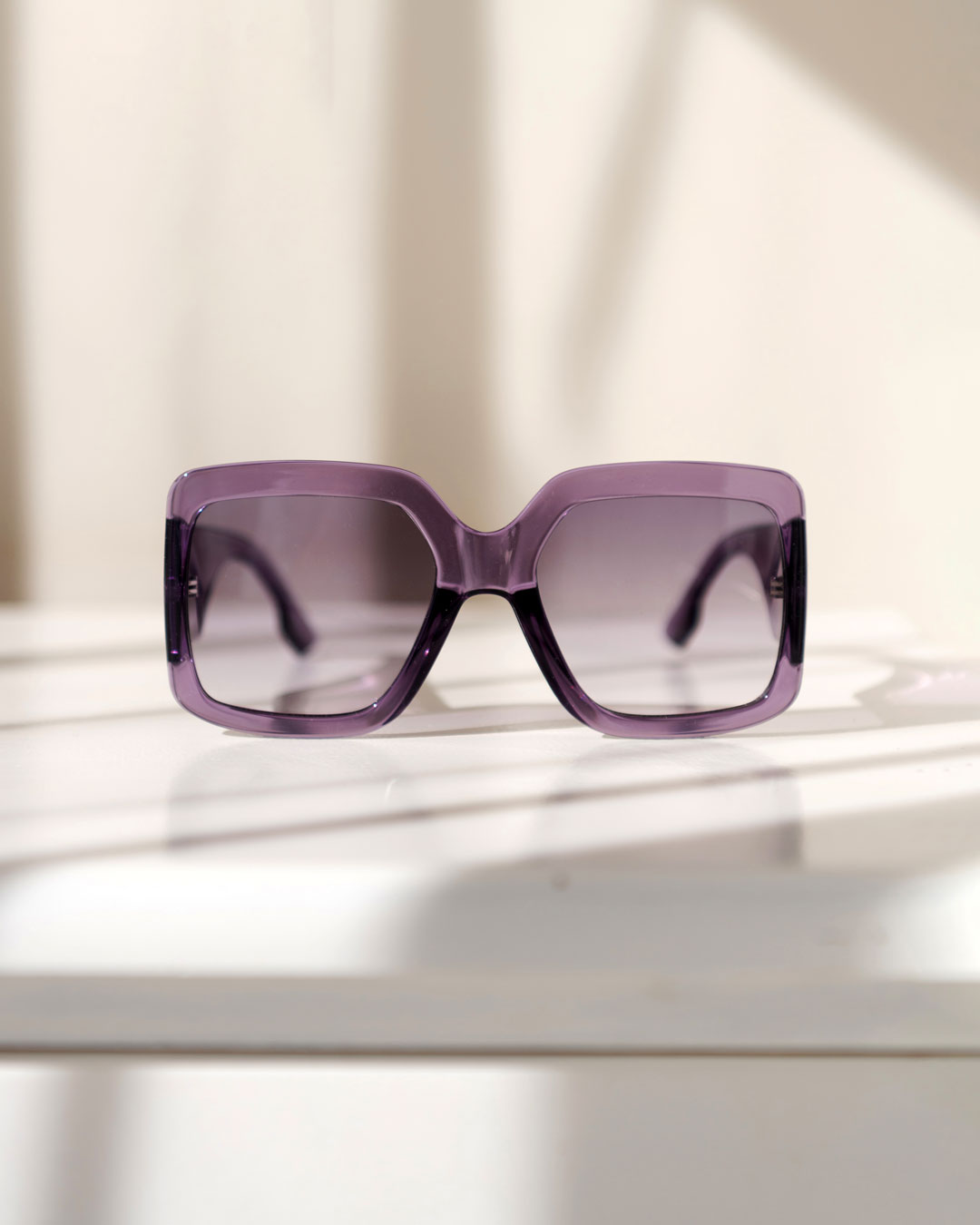 Oversized purple sunglasses with purple lens tints rest on top of a white surface.