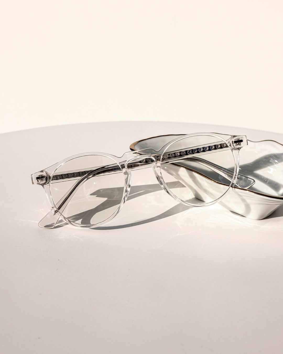 Panto framed glasses with a clear design rest against a white jewellery holder.