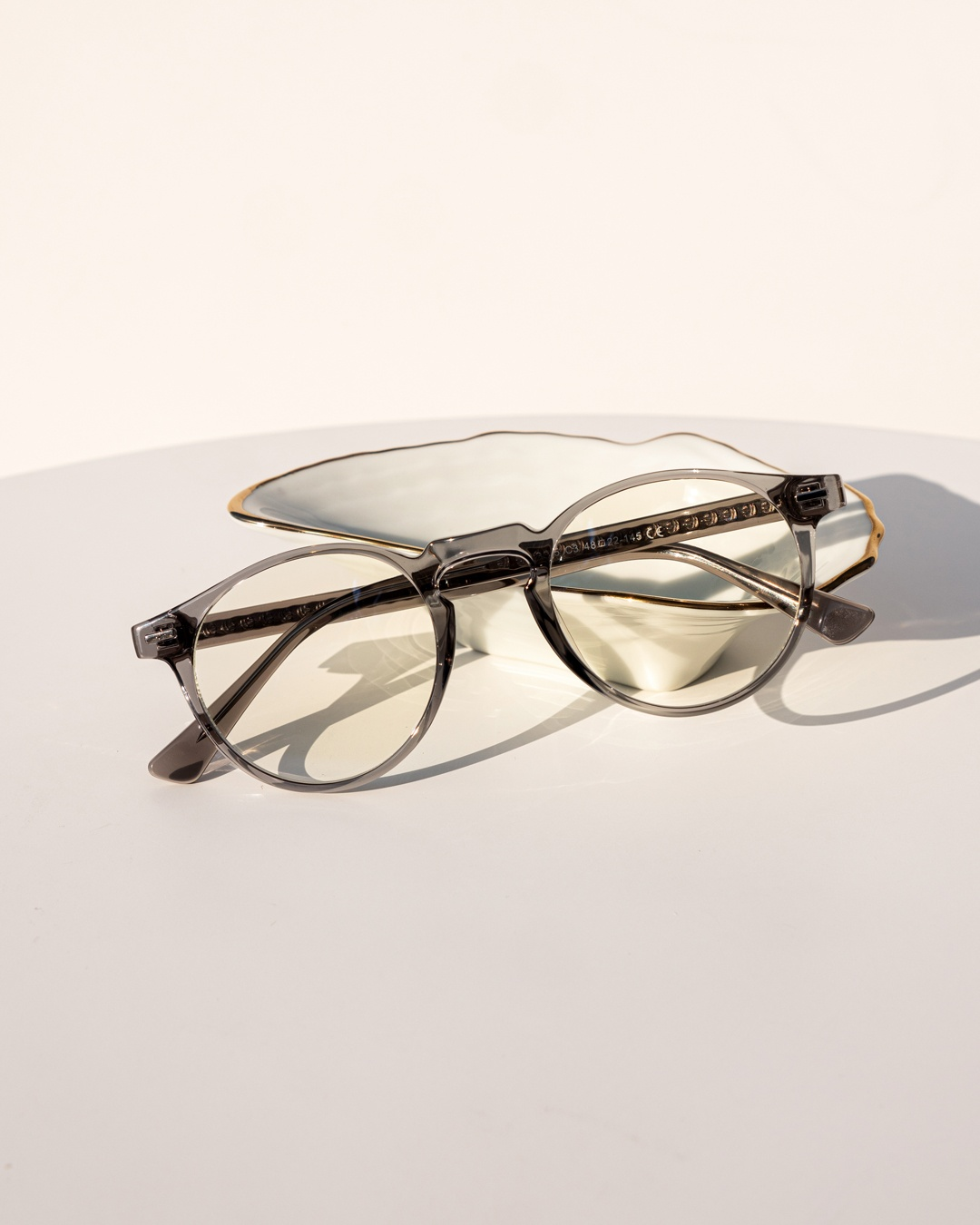 Panto Frame Glasses with a grey transparent silhouette rest against a white jewellery holder.