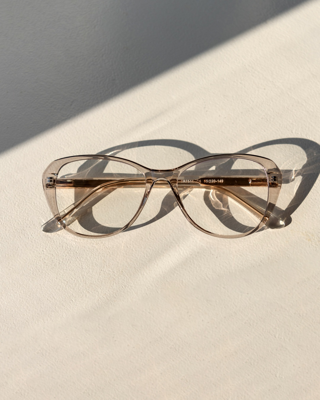 Butterfly framed glasses with a grey, transparent frame rest on a white surface.